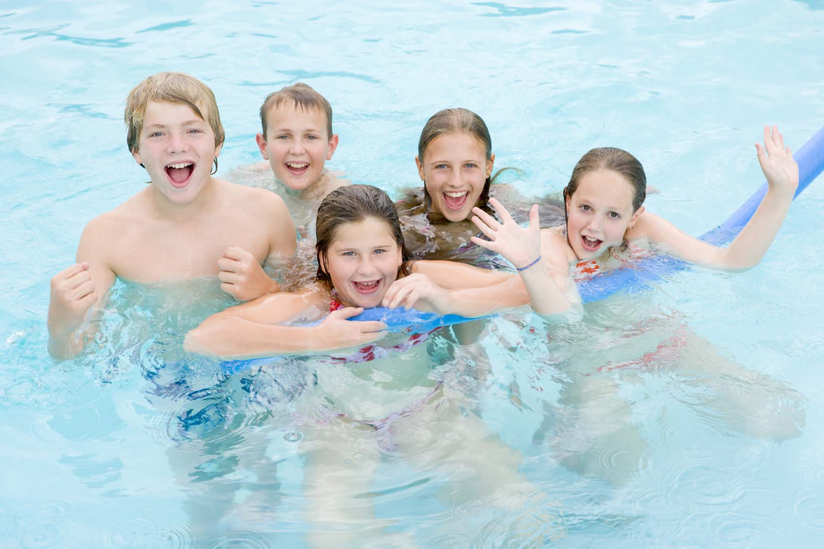 Kids with noodles smiling and laughing in pool